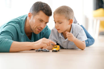 Man and boy playing with die-cast cars
